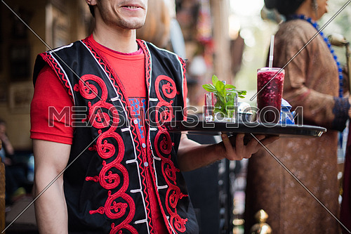 Young middle eastern waiter with traditional refreshing drink on a platter
