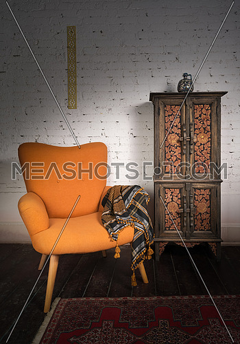 Living room corner including vintage orange armchair, ornamented cupboard and ornate scarf on a red carpet, dark wooden floor and white bricks wall