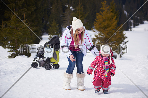 happy family on winter vacation, mom and cute little girl have fun and slide while snow falkes falling