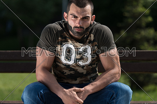 Man In A Shirt Sitting In The Park And Relaxing