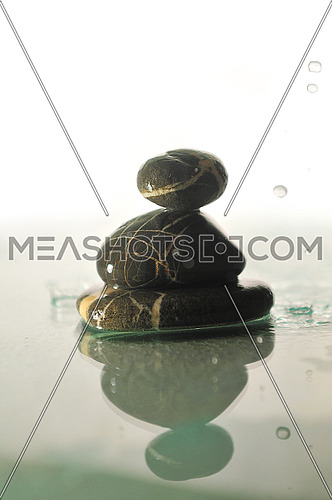 isolated zen stones in perfect harmony with falling and splashing water dropsisolated wet zen stones with splashing  water drops  representing concept of natural balance and perfect harmony