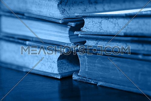 Close up stack of six old vintage classic leather hardcover books on table, blue toned, low angle view