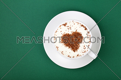 Close up one full white cup of frothy latte cappuccino coffee with heart shaped brown chocolate art, on saucer on green table background, elevated top view, directly above