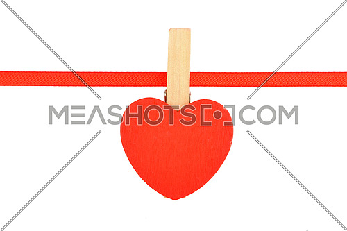 Red painted wooden heart with clothes pin on textile ribbon isolated on white background