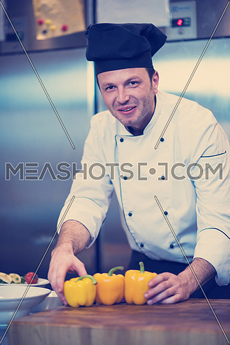 chef holding fresh peppers for vegetable salad in restaurant kitchen