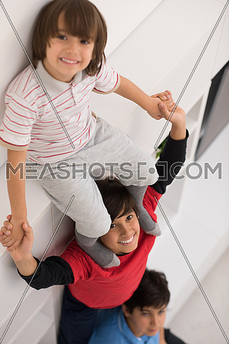 happy young boys having fun and posing line up piggyback in new modern home top view