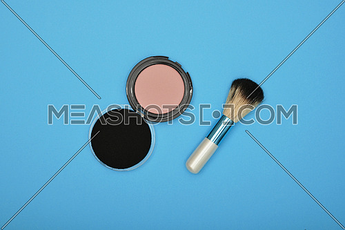 Close up set of face makeup blush, sponge and brush over blue background, elevated top view, directly above