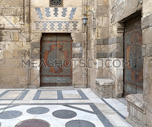 Two perpendicular aged doors at the main courtyard of Al-Sultan Al-Zahir Barquq mosque. Al-Moez Street, Old Cairo, Egypt