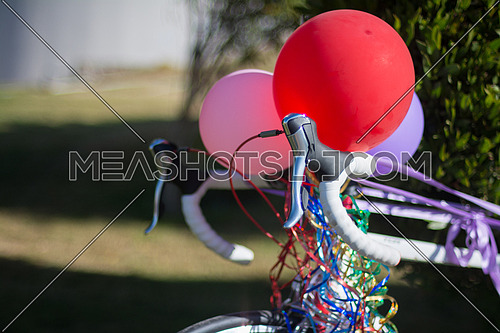 A bicycle decorated with ribbons and balloons in a garden