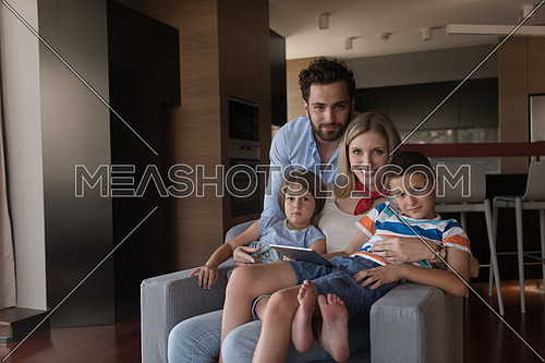 happy couple spending time with kids using tablet computer on an armchair  at home