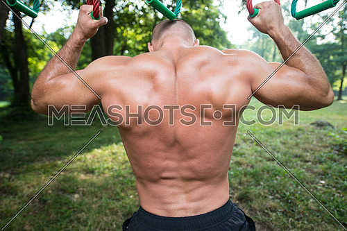 Close-Up Muscular Built Young Athlete Working Out In An Outdoor Gym - Doing Chin-Ups