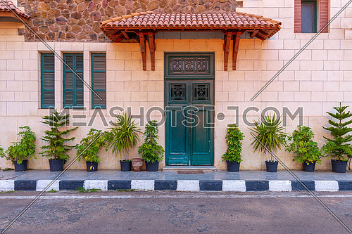 Facade of the clock tower in Montaza public park with green wooden door with red tile canopy above and window shutters on stone bricks wall, Alexandria, Egypt