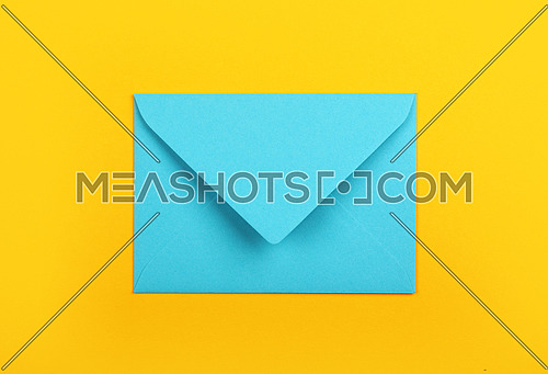 One closed blank pastel blue paper envelope over vivid yellow background, flat lay, directly above