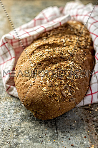 a loaf of whole grain bread wrapped in a cloth