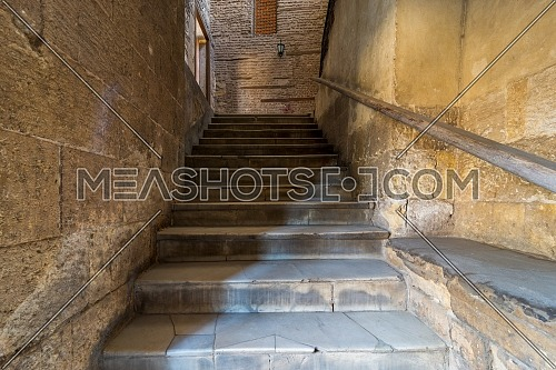 Day shot of old narrow stone staircase leading to stone bricks wall with closed window, Prince Taz Palace, Old Cairo, Egypt