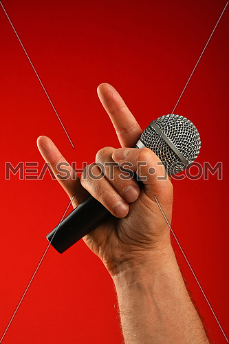 Man hand holding voice microphone with devil horns rock metal gesture sign over red background, front view