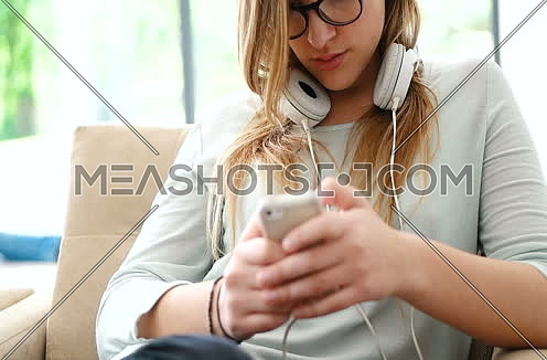 woman sitting on sofa and using smart phone