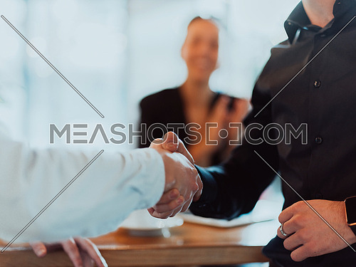 Business people or lawyers shaking hands finishing up meetings or negotiations in sunny offices. Business handshake and partnership