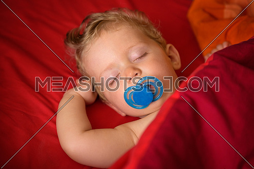Infant  boy eight month old sleeping with soother in his mouth in red background,close up.