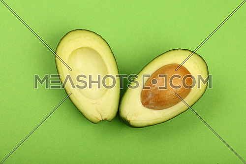 Two halves of one fresh ripe cut avocado with pit stone on green paper background, detail, close up, elevated top view