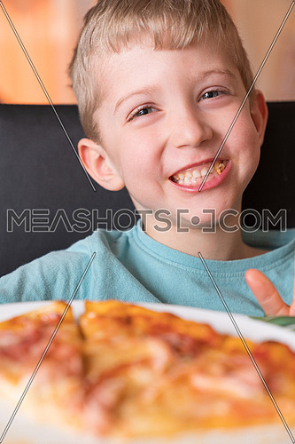 Beautiful happy young boy smiling and eating fresh made pizza,She sit at black chair, He has blonde hair.