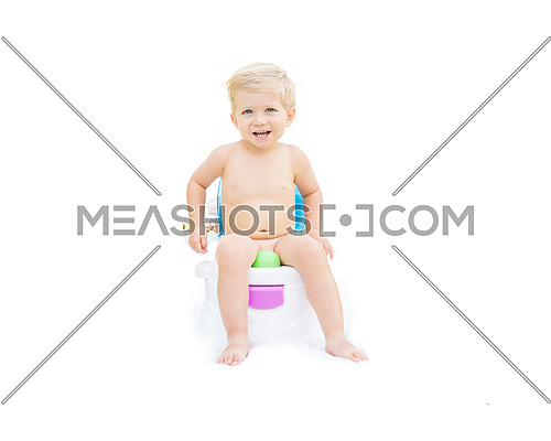 Infant boy, white caucasian smiling and sitting on the potty with white background.