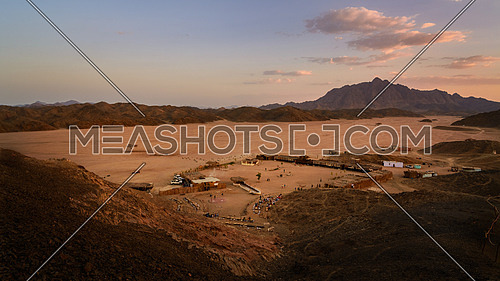 In the picture a beautiful view of a valley in the Egyptian desert at sunset a few kilometers from Marsa Alam, foreground a Bedouin village frequented by many tourists and background the rock mountains.