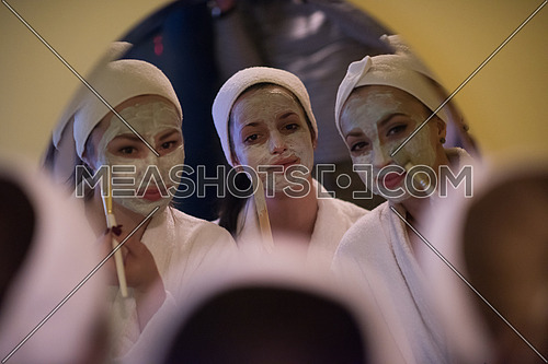a group of young beautiful women looking in the mirror while putting face masks in the bathroom