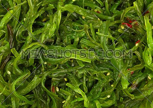 Extreme close up background of green wakame seaweed salad, elevated top view, directly above