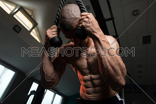 Young Man Performing Abdominals Exercising On Cable Machine In A Fitness Club