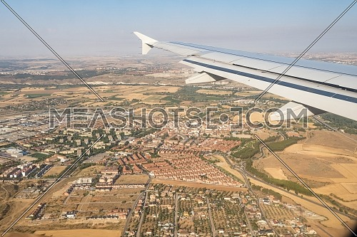Looking through aircraft window during flight. Aircraft wing over blue skies and cityscape