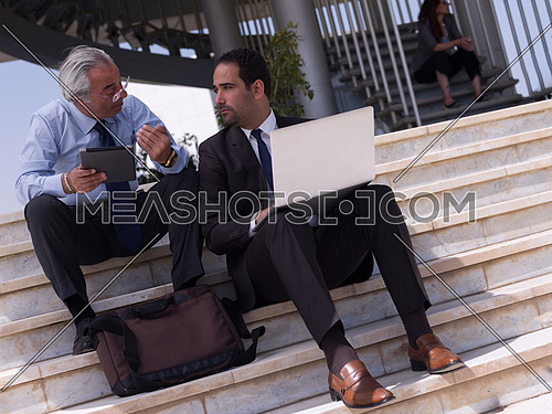 business people group sitting on steps and have meeting and discussinon   using laptop and tablet computer to online check plans and projects