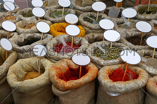 Close up canvas bags of assorted spices with copy space of blank price tags on retail display of market stall, high angle view