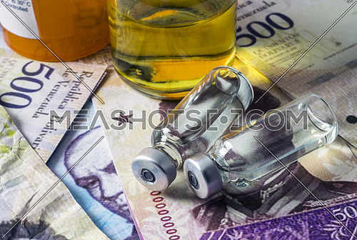 Vials with medication on banknotes Bolivarian, shady deal of medicines in full crisis of Latin American country, conceptual image