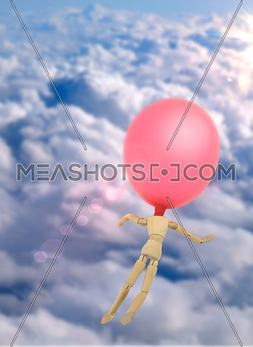 Doll made of wood with balloon in the head flies through the sky, conceptual image