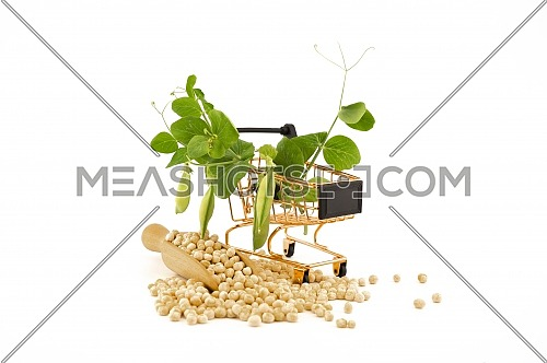 Dried peas spilling from a wooden scoop and fresh plant with pods in a small shopping cart isolated on a white background