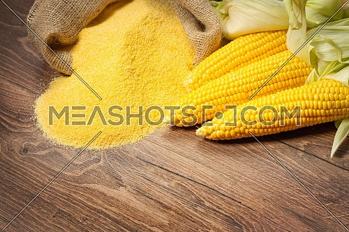 Ripe young sweet corn cob,on left stack cornmeal on wooden background, copy space.Gluten free food concept