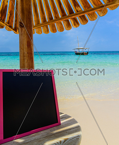 In the picture a Zanzibar beach which is a small blackboard with the words \
