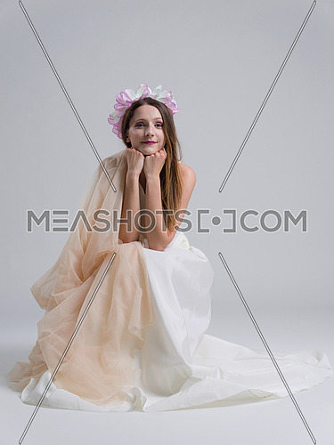 Beautiful young bride sitting in a wedding dress isolated on a white background