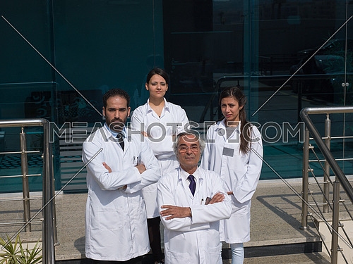 smiling team of doctors in front of modern hospital