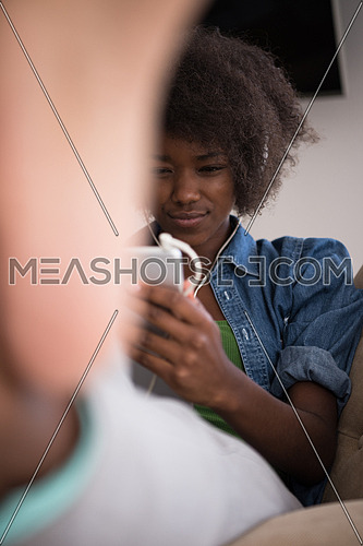 young beautiful African American woman enjoys listening to music with headphones and tablet in your armchair in her luxury home
