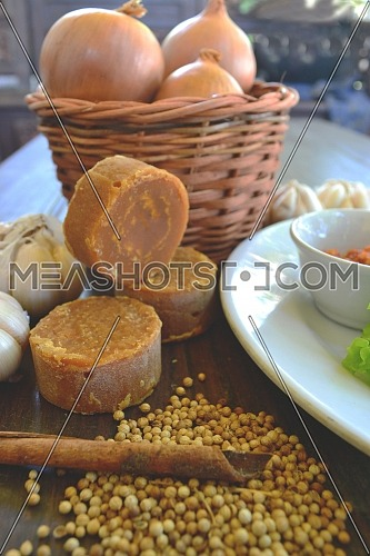 Coriander seeds, cinnamon and palm sugar on a wooden table, Indonesian spices