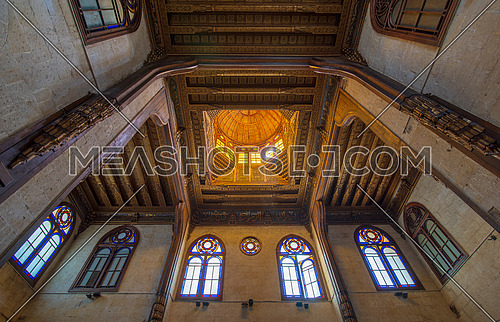 Wooden decorated dome mediating ornate ceiling with floral pattern decorations and stained glass windows at Sultan al Ghuri Mausoleum, Cairo, Egypt