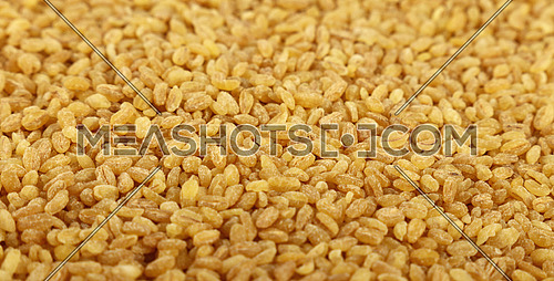 Yellow traditional bulgur (bulghur, burghul) big grains of durum wheat, close up pattern background, high angle view, selective focus