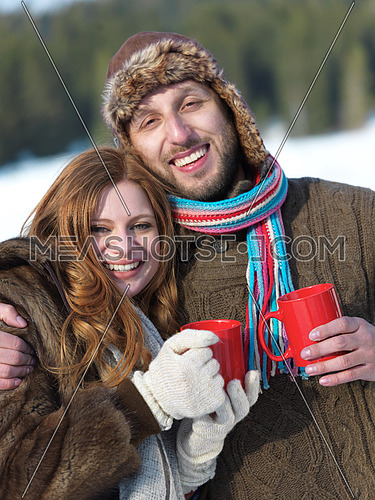 portrait of happy young couple outdoor on winter day drinking warm tea with fresh snow in background