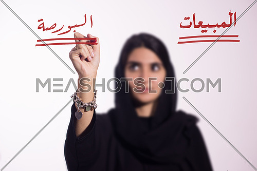 Arabian middle eastern business woman writing with a marker on virtual screen in arabic Stock and sales isolated on white background