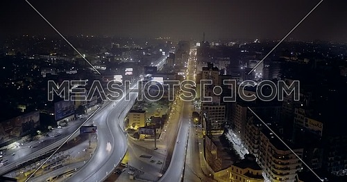 Aerial shot flying around 6 of October Bridge over Abd Elmonan Reyad Bus Station At Tahrir Area in cairo at night