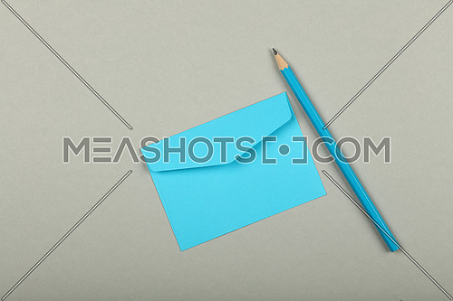 One closed blank pastel blue paper envelope and wooden pencil over grey background, flat lay, directly above