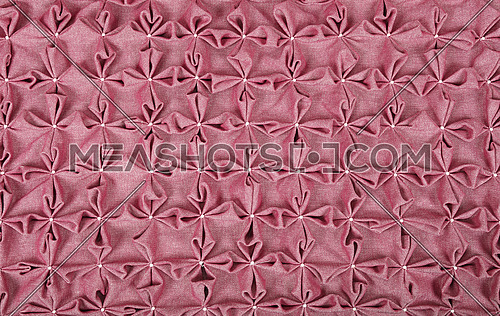 Close up background texture of purple pink textile puffs for Canadian smocking upholstery decoration with beads