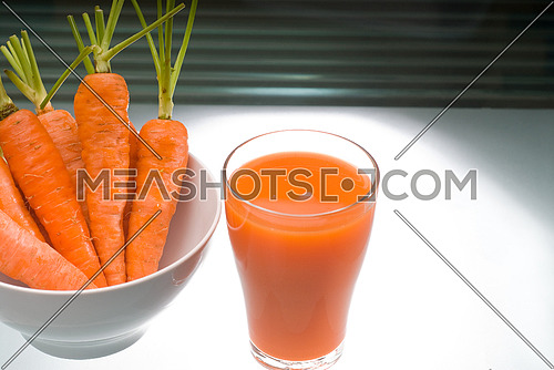 fresh and healty carrot juice unfiltered over a light table